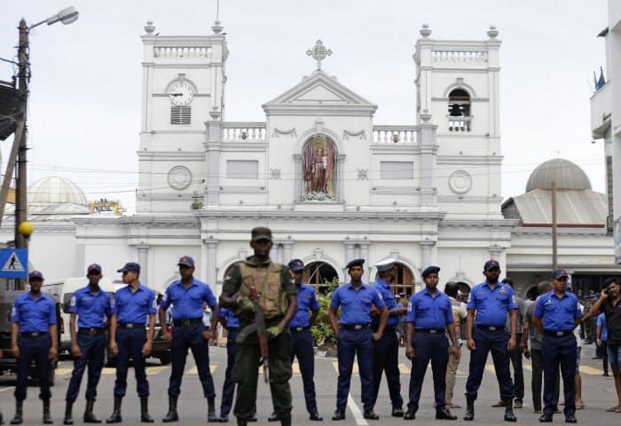 爆発があった教会前で警戒に当たる兵士ら(21日、コロンボ)=AP