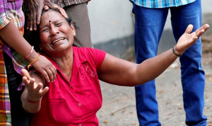 コロンボで犠牲者の死を嘆く親族(21日)=ロイター