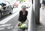 市営の路線バスが歩行者をはねた事故現場で献花し手を合わせる女性(22日午前、神戸市中央区)=目良友樹撮影