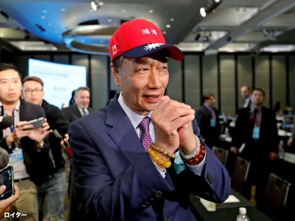 4月16日、鴻海と国民党のロゴをあしらった野球帽をかぶり、台湾関係法の40周年式典に参加する郭氏=ロイター