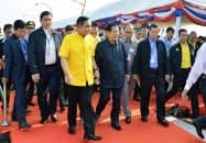 22日、国際鉄道開通の調印式に臨むタイのプラユット暫定首相(中央左)とカンボジアのフン・セン首相(同右)=タイ・カンボジア国境