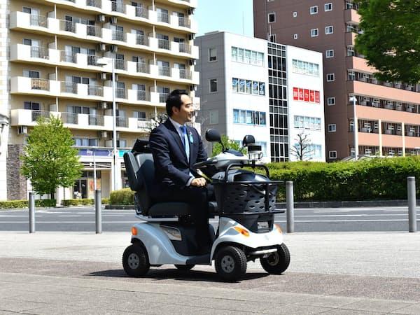 自動運転の電動車いすに試乗する茨城県つくば市の五十嵐立青市長(22日、同市)