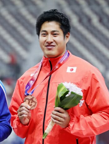 男子やり投げで銅メダルを獲得し、表彰式で笑顔の新井涼平(22日、ドーハ)=共同
