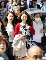 気温が上がり、コートを手に歩く女性(22日、名古屋市中村区)