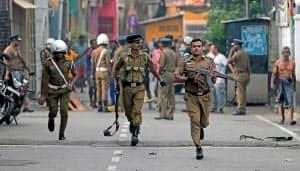 コロンボの爆発現場を調べる警察官(22日)=ロイター