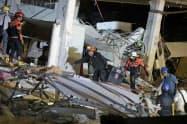 地震で倒壊した建物で被害者の有無を調べる救助隊(23日、フィリピン北部パンパンガ州)=AP