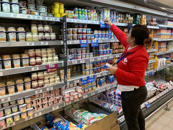 スーパーで商品の値札を張り替える店員(22日、ブエノスアイレス)