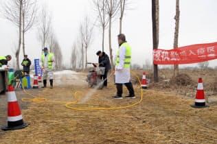アフリカ豚コレラが見つかった農場周辺で防疫作業にあたる警察官ら(2月、中国・河北省)=ロイター