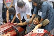 23日、スリランカ西部ネゴンボでテロ犠牲者の埋葬に立ち会う人々=ロイター