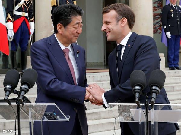 エリゼ宮で共同記者発表するマクロン仏大統領(右)と安倍首相(23日、パリ)=ロイター