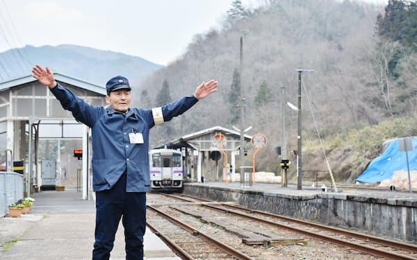 両手を大きく振り、遠ざかる列車を見送る(広島県庄原市のJR備後落合駅)=大岡敦撮影