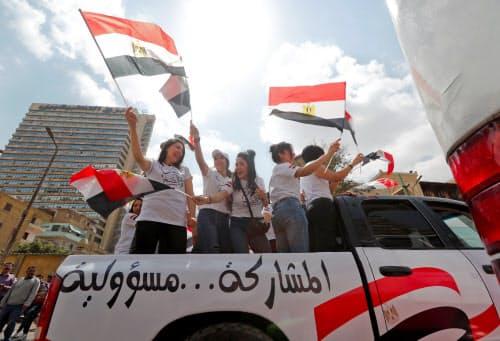 エジプトの国民投票で国旗を振る人たち(20日、カイロ)=ロイター