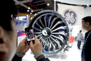 GEのエンジンの写真を撮る男性(18年11月、上海で)=ロイター