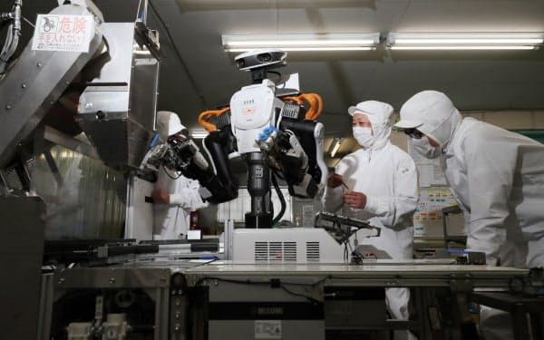 煎餅などを製造する三州製菓でもカワダロボティクスのロボットを導入。「調子はどうかな。今日も一緒に働いてくれるかな?」と従業員が見守る。(埼玉県春日部市)