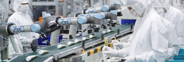次々とラインに流れてくる歯磨き粉を箱に入れていくユニバーサルロボット製のロボット。人と接触すると停止する安全装置が備えられている(相模原市の日本ゼトック相模原事業所)