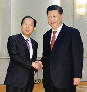 会談を前に、中国の習近平国家主席(右)と握手する自民党の二階幹事長(24日、北京の人民大会堂)=代表撮影・共同