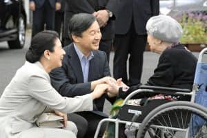 仮設住宅を訪問し、被災者の女性の手を取り懇談する天皇、皇后両陛下(2018年9月、福岡県朝倉市)=共同