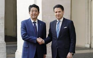 首相府に到着し、イタリアのコンテ首相(右)と握手する安倍首相(24日、ローマ)=共同