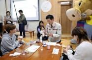 液体ミルクの備蓄などが始まった「道の駅阿蘇」で、グリコの担当者(中央)から説明を受ける母子(24日、熊本県阿蘇市)=共同