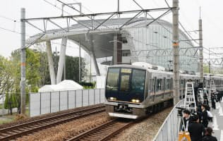 脱線事故現場の横を通過するJR福知山線の車両(25日、兵庫県尼崎市)