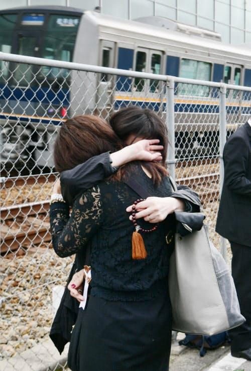 脱線事故現場近くで抱き合い、犠牲者を悼む人たち(25日午前、兵庫県尼崎市)