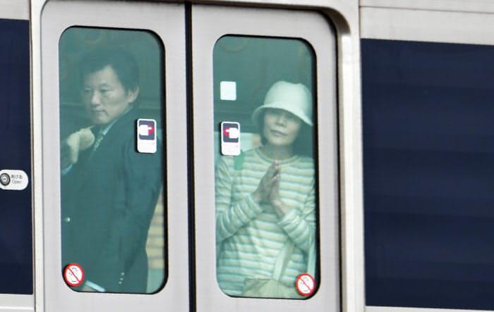 脱線事故現場を通過する電車内で手を合わせる人たち(25日午前、兵庫県尼崎市)