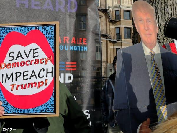ボストンでの街頭デモでは、トランプ大統領弾劾を訴えるプラカードを持つ参加者(左)とトランプ大統領の支持者(右)が肩を並べた=ロイター