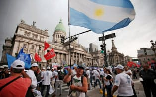 4日、政府の経済政策に反対してブエノスアイレス市内をデモ行進するアルゼンチンの労組メンバーら=ロイター