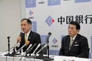 記者会見する中国銀の宮長頭取(右)と加藤専務(25日、岡山市)