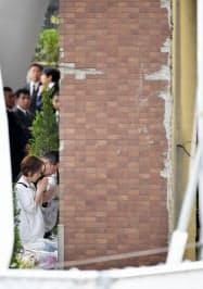 電車が衝突したマンションを訪れ、手を合わせる人たち(25日午後、兵庫県尼崎市)