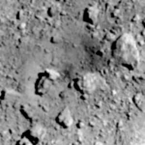 探査機はやぶさ2が小惑星りゅうぐうにつくったクレーター(中央右上の暗い色のへこんだ部分)=JAXAなど提供