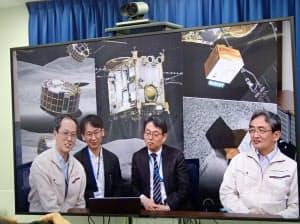 テレビ会議システムを使った記者会見で笑顔を見せるJAXAの津田雄一プロジェクトマネージャ(左)ら(25日、東京都千代田区)