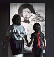 再オープンした原爆資料館本館の入り口に展示された、焼け跡に立つ少女の写真(25日午前、広島市)=共同