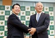 新社長に決まり握手する九州FGの笠原氏(左)と上村社長(25日、熊本市中央区)