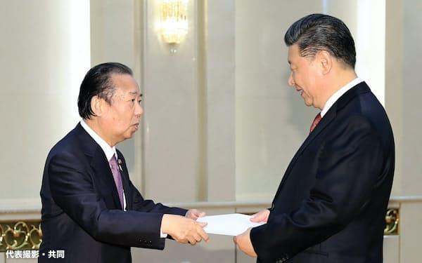 会談を前に、中国の習近平国家主席(右)に安倍首相からの親書を手渡す自民党の二階幹事長(24日、北京の人民大会堂)=代表撮影・共同