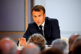 25日、新たな生活支援策を発表したマクロン仏大統領(パリ)=ロイター