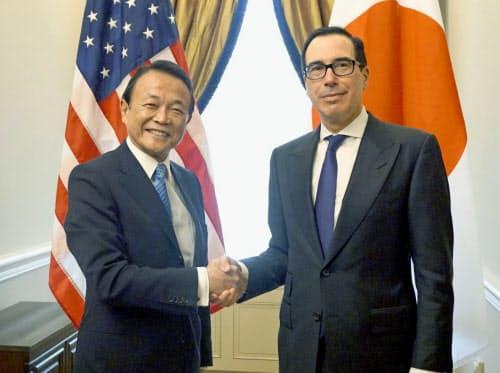 握手する麻生財務相(左)とムニューシン米財務長官(25日、ワシントン)=共同