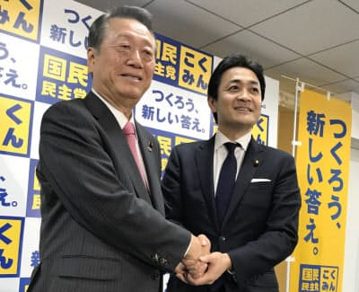 握手する国民民主党の玉木代表(右)と自由党の小沢共同代表(26日未明、東京・永田町)