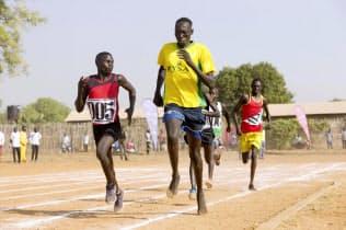 南スーダンで開かれたスポーツ大会で、はだしでグラウンドを走る選手ら(久野真人氏撮影、JICA提供)=共同