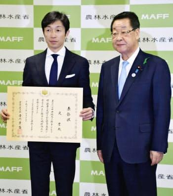 農林水産大臣賞を受賞し、表彰状を手にする武豊騎手。右は吉川農相(26日午後、東京都千代田区)=共同