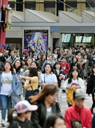 10連休となるゴールデンウイークが始まり、USJに向かう人らでにぎわうJRユニバーサルシティ駅前(27日、大阪市)=共同