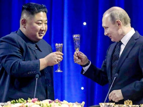 夕食会で乾杯する北朝鮮の金正恩委員長(左)とロシアのプーチン大統領=25日、ロシア・ルースキー島(タス=共同)