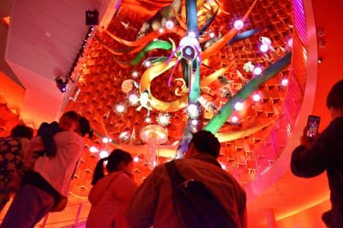太陽の塔内部にある「生命の樹」にカメラを向ける来館者(4月11日、大阪府吹田市)