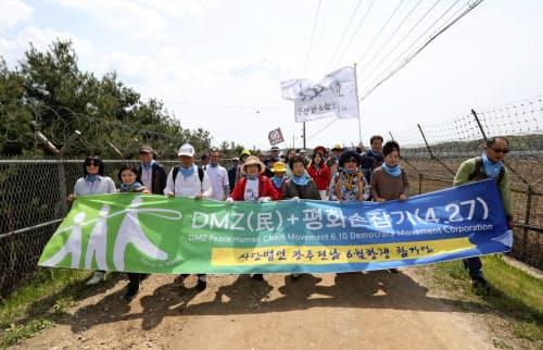 27日、南北首脳会談1周年を祝い板門店近郊で行進する韓国市民=AP