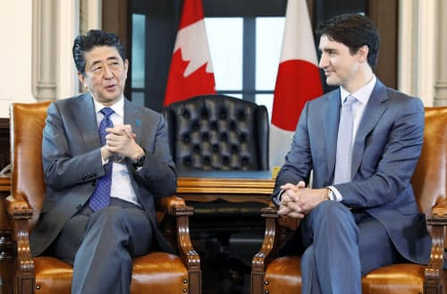 会談する安倍首相(左)とカナダのトルドー首相(28日、オタワ)=共同