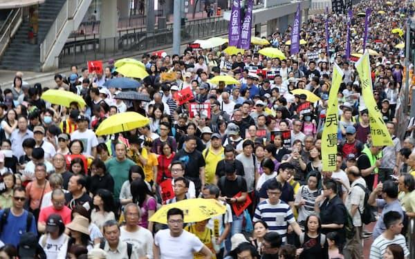 条例改正案に反対するデモの参加者には雨傘運動」のシンボルである黄色い傘をさす人も