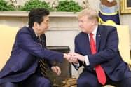 握手する安倍首相(左)とトランプ米大統領(26日、ワシントンのホワイトハウス)=共同