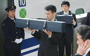 伊勢神宮に退位を報告し、帰京する天皇、皇后両陛下に随行する侍従。三種の神器のうち、「剣」と「璽」が入ったケースを運ぶ(4月19日、JR名古屋駅)