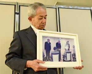 上皇ご夫妻が訪問した時の写真を手に話す村田さん(4月22日、広島市)