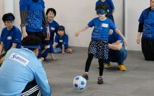 ブラインドサッカーを体験する、ANAホールディングスの社員と家族ら(東京都港区)